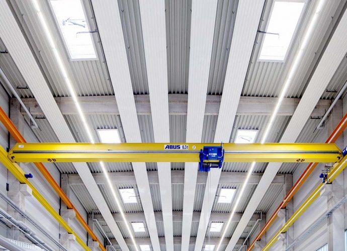 Insgesamt 850 Mitarbeiter arbeiten auf dem Stammgelände der Reifenhäuser GmbH & Co. KG in Troisdorf. Um die Effizienz der Wärmeverteilung und die Behaglichkeit für die Mitarbeiter zu optimieren, wurden in allen neun Werkshallen auf dem Gelände nun über vier Kilometer Deckenstrahlplatten installiert. Eine Investition, die sich über enorme Energieeinsparungen auszahlt. Deckenstrahlplatten funktionieren nach dem Strahlungsprinzip: Die Infrarotstrahlung, welche die von warmem Wasser durchströmte Platte abgibt, verwandelt sich erst beim Auftreffen auf einen Körper oder Gegenstand in Wärme. Weil damit nicht die gesamte Luftkubatur erhitzt und umgewälzt werden muss, sind Energieeinsparungen über 40 Prozent gegenüber konventionellen Wärmeverteilsystemen möglich.